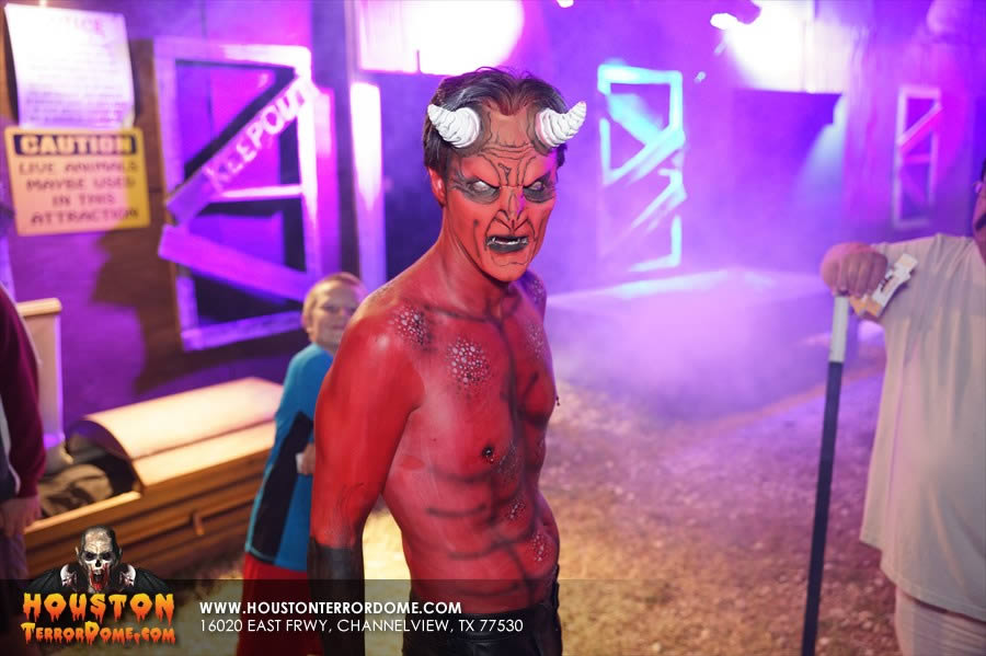 The Devil with full face paint out front of haunted house