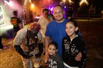 Young kid stays close to dad while waiting in line at the Haunted house